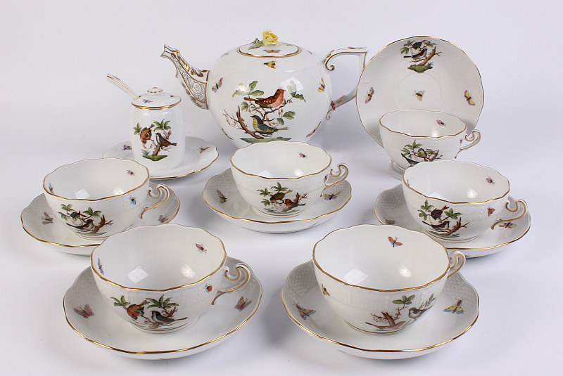 Čajový servis pro 6 osob, porcelán, 8 kusů, obsahuje 6 koflíků s miskami, konvice, nádoba na med s víčkem a lžičkou, pestře malovaný motiv motýlků, hmyzu a ptáčků na větvích, plastický okraj Ozier, Maďarsko, Herend, modrá tištěná značka, dekor Rotschild Oiseaux, 80. léta 20. století, perfektní, nepoužitý stav, vyvolávací cena 18 000 Kč Foto: archiv Dorotheum, oficiální zdroj